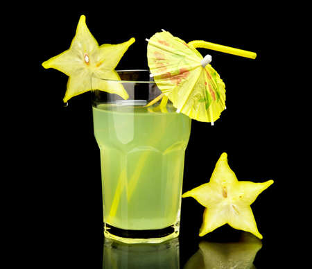 Close-up view of mojito drink,carambola fruit with umbrella on a party on black background