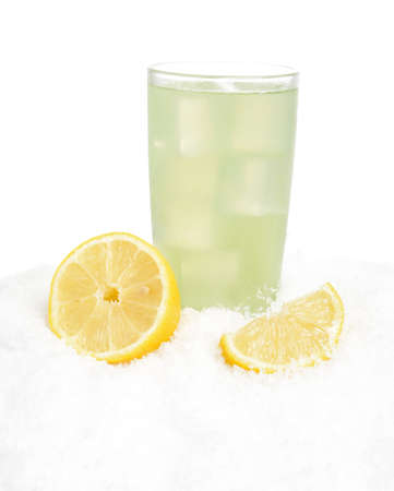 citrons: Glass of lime juice with ice cubes,lemons halves on snow on white background
