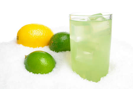 citrons: Glass of lime juice with ice cubes,limes,lemon on snow on white background