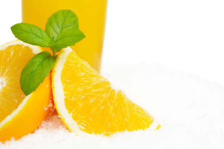 Cropped image of orange juice with ice cubes and orange fruit with citrus leaves on ice on white background Stock Photo