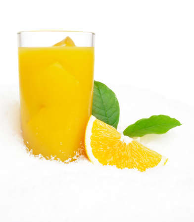 Orange juice with ice cubes and orange fruit with citrus leaves on ice on white background