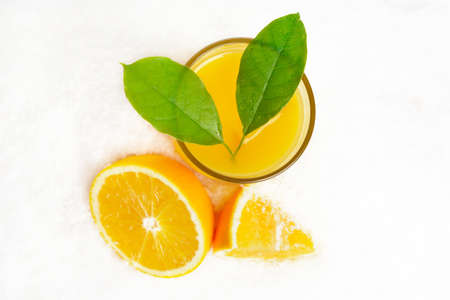 View from above orange juice with ice cubes,leaves on ice on white background Stock Photo