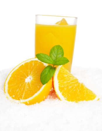 Orange juice with ice cubes and orange fruit with citrus leaves on ice on white background