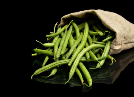 flaxen: Stack of green beans in linen sack on black background