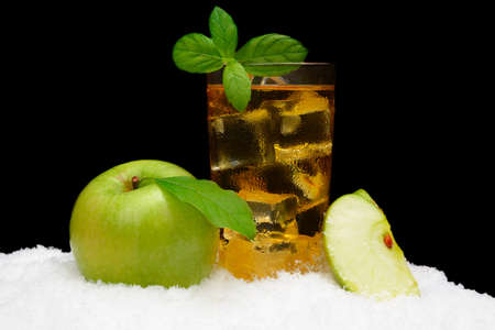 Frosty apple juice,ice cubes and whole apple with apple leaves on black background on snow