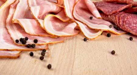 uncooked bacon: Gastronomy ingredients-Slices of pink bacon and salami with black peppercorn on wooden board background