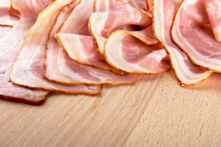 streaky: Assorted slices of fat pink bacon on wooden plank