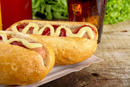 ketchup bottle: Hot dogs in the tray with ketchup with cola,lettuce on wooden board