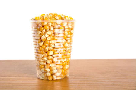 Plastic cup full of corn seeds on white background