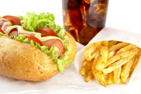 servilleta de papel: perro caliente clásico con ingredientes con patatas fritas con el vidrio de cola en la servilleta en el fondo blanco