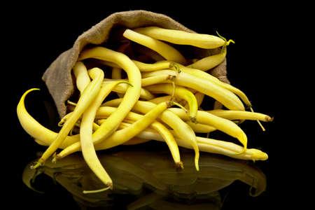 Stoh žlutých fazolí v lněném pytli na černém pozadí