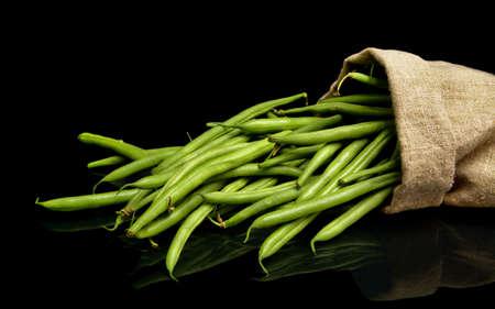 Stack zelených fazolí v lněném pytli na černém pozadí
