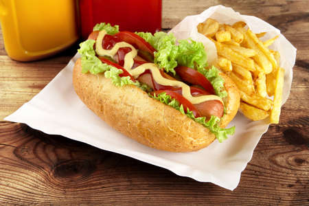 Single hot dog with ingredients with french fries on the tray on wooden desk background