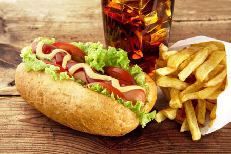 servilleta de papel: Classic hot dog with ingredients with french fries with glass of cola on serviette on wooden desk Foto de archivo