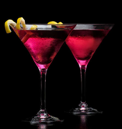 Pink cosmopolitan drinks isolated on black background