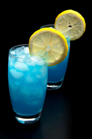 Blue  cocktails with slice of citrus with ice cubes isolated on black Stock Photo
