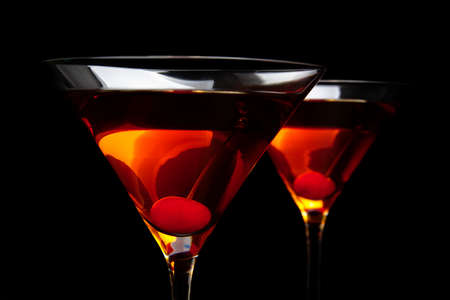 Closeup manhattan drinks with red cherry on black background