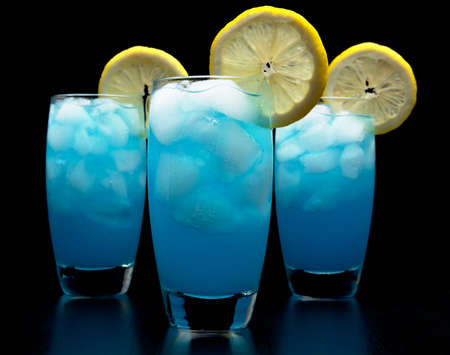 Blue  drinks with slice of citrus with ice cubes isolated on white Stock Photo