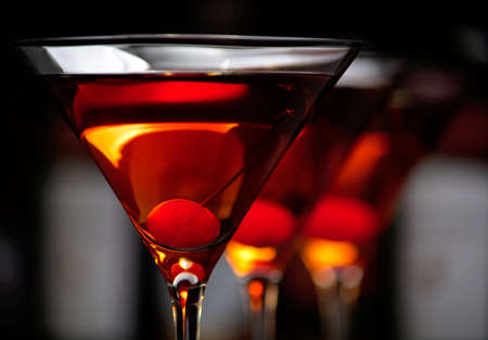 Cropped manhattan drinks with red cherry with club in the background Stock Photo