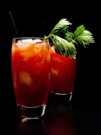 Bloody Mary drinks with ice cubes and celery isolated on black background Stock Photo