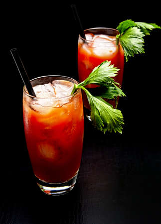 Bloody Mary cocktails with ice cubes and celery isolated on black background