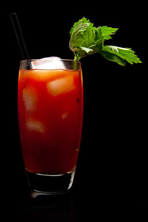 Bloody Mary with ice cubes with celery isolated on black background