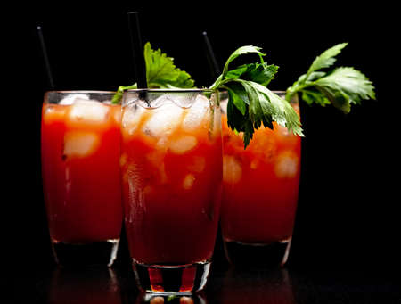 Red Bloody Mary drinks with ice cubes with celery isolated on black background
