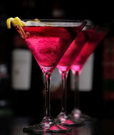 Three cosmopolitan drinks in line in bar on black background