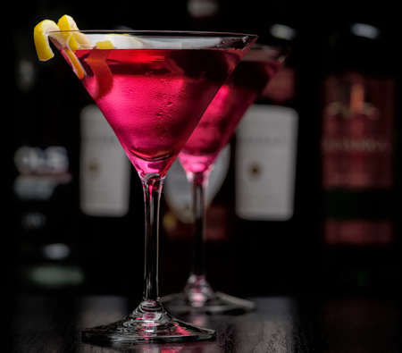 Two cosmopolitan cocktails in bar on black background