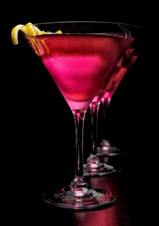 Three cosmopolitan drinks in line on black background
