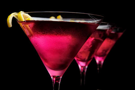 Cropped three cosmopolitan cocktails in line on black background