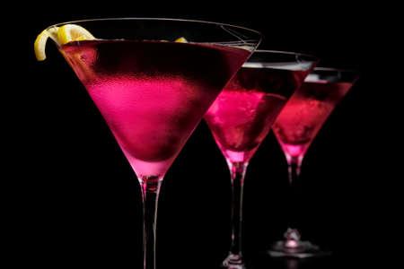 Drei kosmopolitische Cocktails in einer Reihe auf schwarzer Theke und Hintergrund