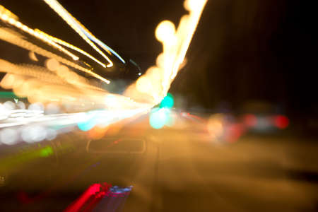 Defocused and motion blurred night scene with traffic lights