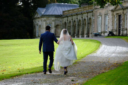 northern ireland: Wedding Couple walking towards a fine manor house in Northern Ireland. The man has a blue suit and brown shoes and the lady is in a wonderful wedding dress with blue shoes.