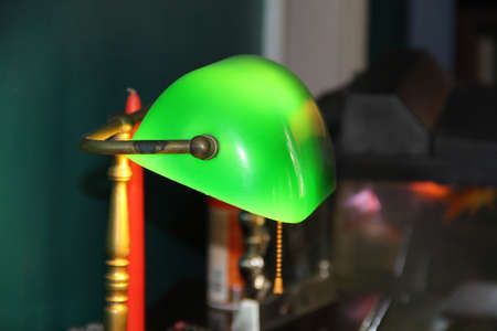 Groene Lamp die op de Oude Bureauachtergrond wordt geïsoleerd Stockfoto