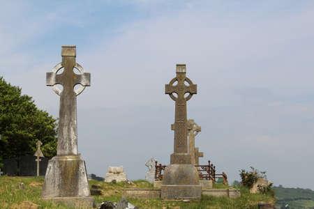 Due vecchie croci celtiche nel cielo azzurro del cimitero irlandese Timoleague o potrebbero essere dovunque in Irlanda Archivio Fotografico - 73679733