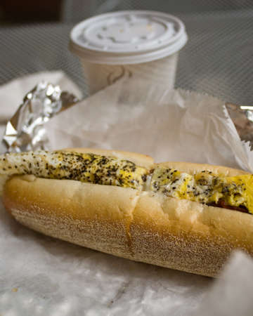 An egg and cheese sub in Philadelphia with a lot of pepper, with cup of coffee