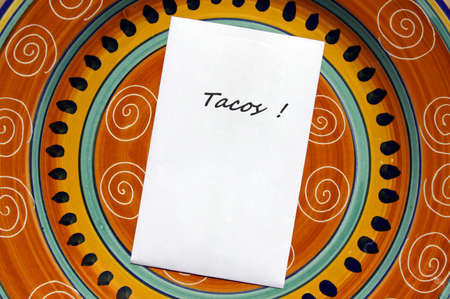 The word TACOS! printed on white paper with copy space on top of colorful Mexican style plate.