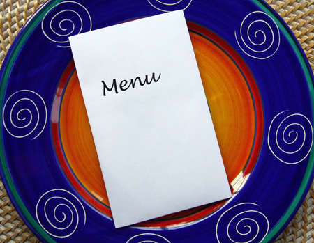 White paper with word MENU and copy space on top of blue Mexican style plate. photo