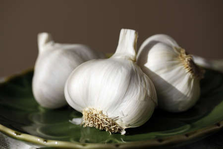 the stinking: Garlic bulbs with roots and skin resting on green plate.