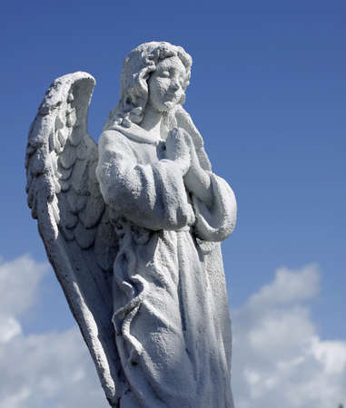 statuary: Large praying angel cemetery statuary against blue sky  Stock Photo