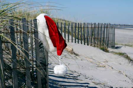 Red and white Santa hat hanging from a wood dune fence on the beach.