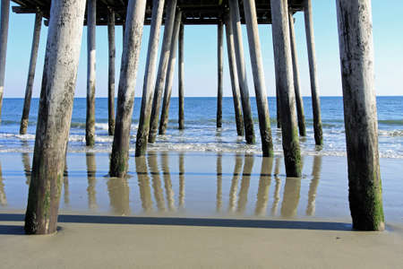 be wet: Color image of fishing pier stilts stretching from the bach to the ocean. Reflection of the stilts. can be seen on the wet sand.