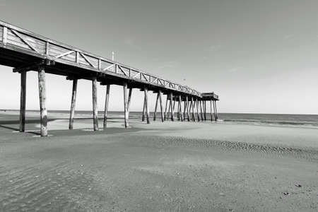 ocean fishing: Black and white image of a fishing pier that stretches across the beach to the ocean.