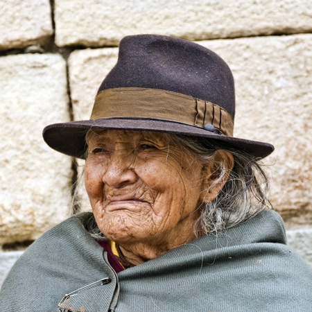 descendants: CUENCA, ECUADOR - MAY 30: Andean indigenous woman standing by an old inca wall in traditional customs on May 30, 2011 in Cuenca, Ecuador. Inca descendants can be found the Andes regions of Ecuador