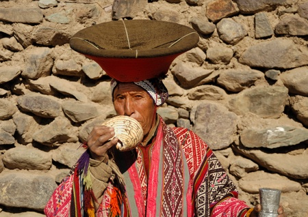"""CHINCHERO, PERU - SEPTEMBER 3: Indigenous man plays shell instrument called """"pututo"""" on September 7, 2007 in Chinchero, Peru. Direct Inca descendants are found in the Cusco andean region."""