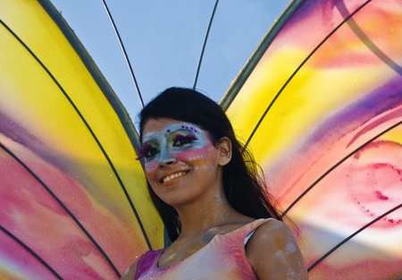 mardigras: SANTO DOMINGO, DOMINICAN REPUBLIC - MARCH 6: Butterfly model waives at the Malecon Carnival on March 6, 2011 in Santo Domingo, Dominican Republic. Exotic customs can be seen at this annual event