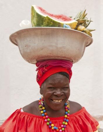 tribu: CARTAGENA, COLOMBIA - el 30 de julio: Palenquera mujer vende fruta el 30 de julio de 2010 en Cartagena, Colombia. Palenqueras son un grupo étnico descendiente único africano que se encuentra en el norte de América del Sur. Editorial