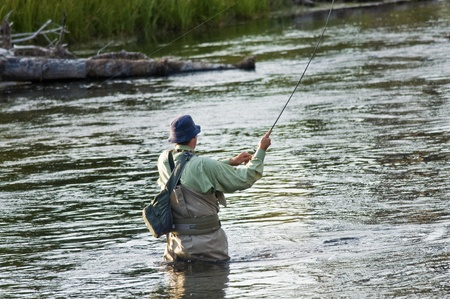fishing rods: MONTANA, USA - SEPTEMBER 4:  Fisherman engaged in fly fishing on the Yellowstone river on September 4, 2009 in Montana, USA. Fly fishing is a  very popular sport in Yellowstone river during summer.