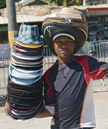 SANTO DOMINGO, DOMINICAN REPUBLIC - MARCH 6: Unidentified child trying to sell colorful hats under the caribbean sun at the